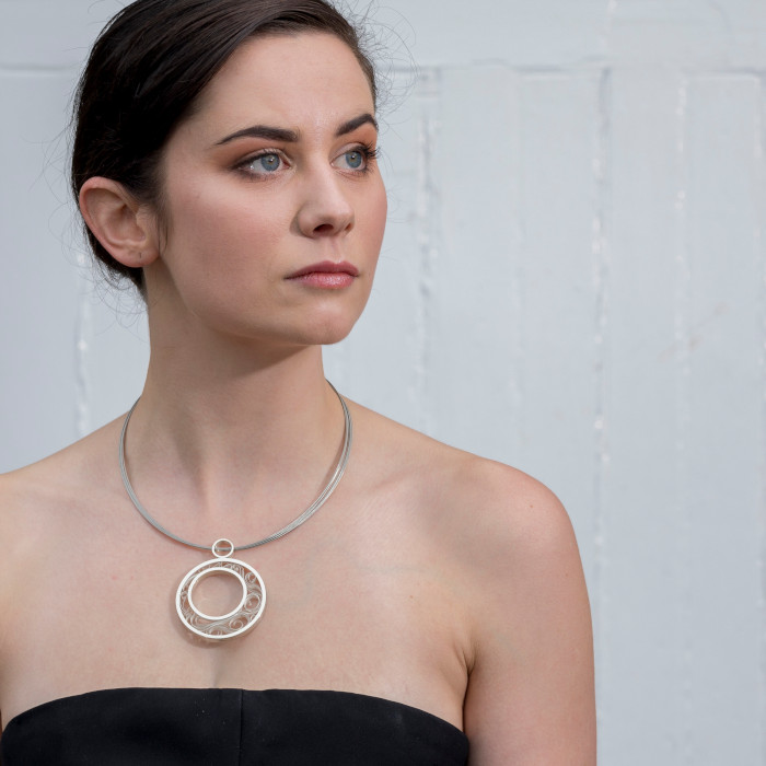 Model wearing a silver pendant with silver ribbons swirling inside a circular frame, designed & created by Doireann O'Riordan